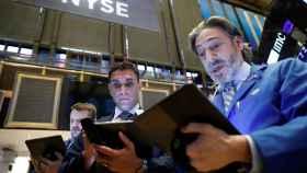 Tres operadores con gesto de asombro en la Bolsa de Nueva York.