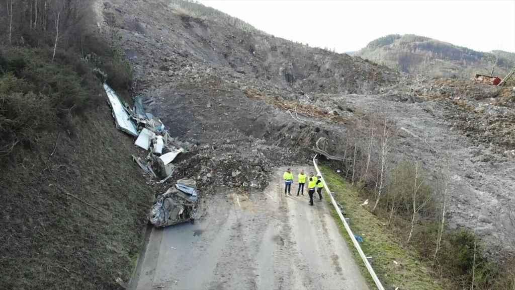 Dos trabajadores continúan sepultados por una montaña de basura.