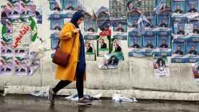 Una mujer iraní pasea delante de los carteles electorales