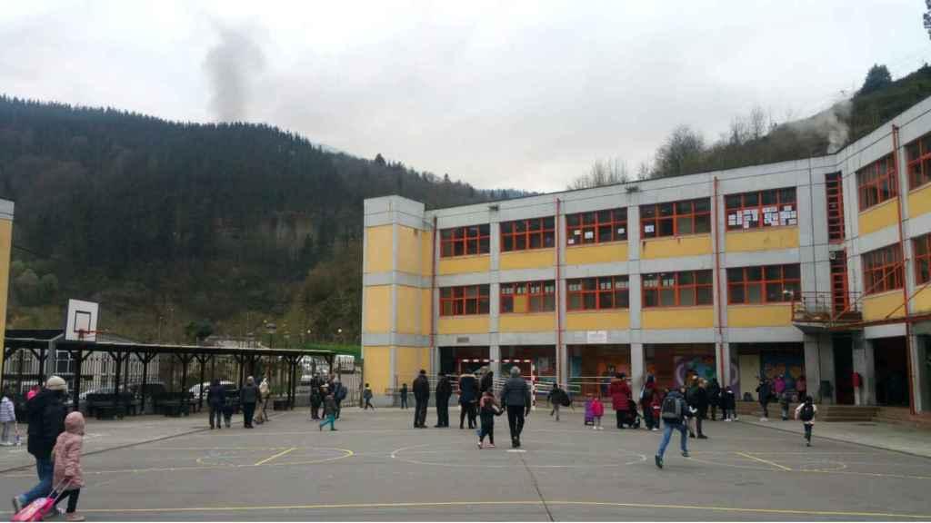 Patio del colegio San Lorenzo de Ermua este viernes. De fondo, el humo tóxico del incendio.