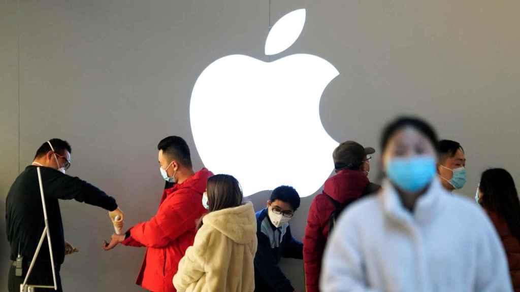 Personas con mascarilla son comprobadas antes de entrar en una Apple Store abierta en Shanghái