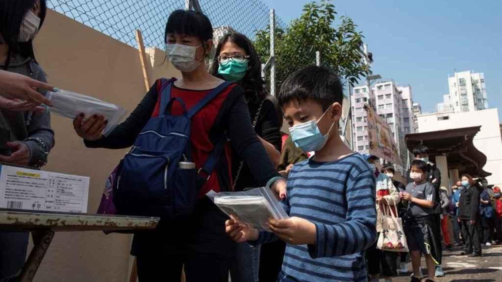 Ciudadanos de Hong Kong hacen cola para recibir mascarillas.
