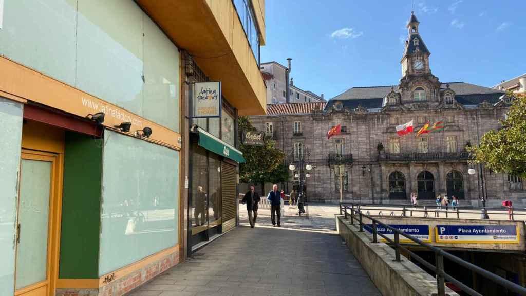 Dos locales comerciales cerrados y, de fondo, el Ayuntamiento de Torrelavega