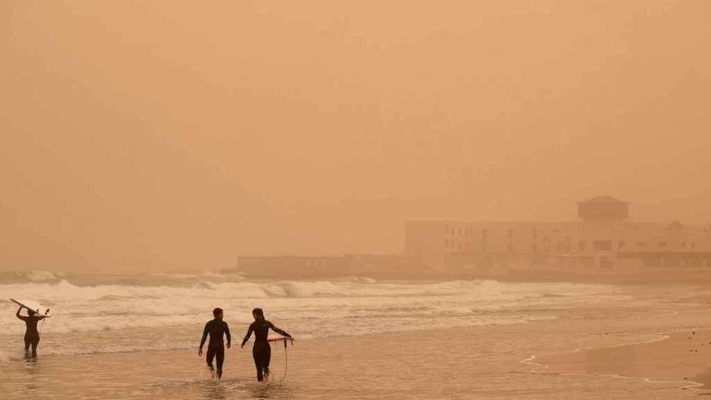 Surfistas en Puerto del Rosario (Fuerteventura) bajo la calima. EFE/Carlos de Saá.