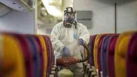 Un hombre desinfecta un avión.