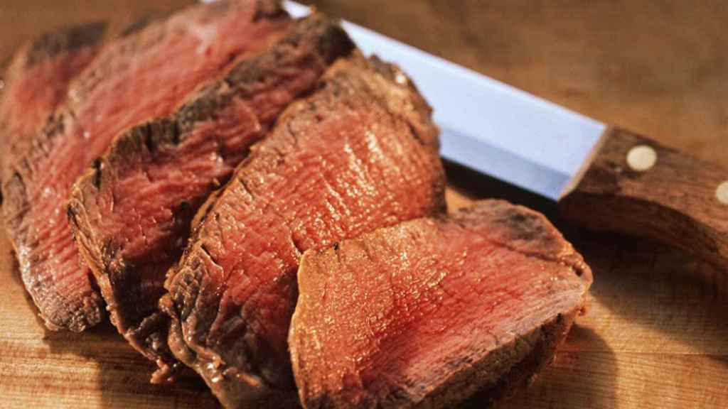 Cortes de carne roja con su jugo rojizo.
