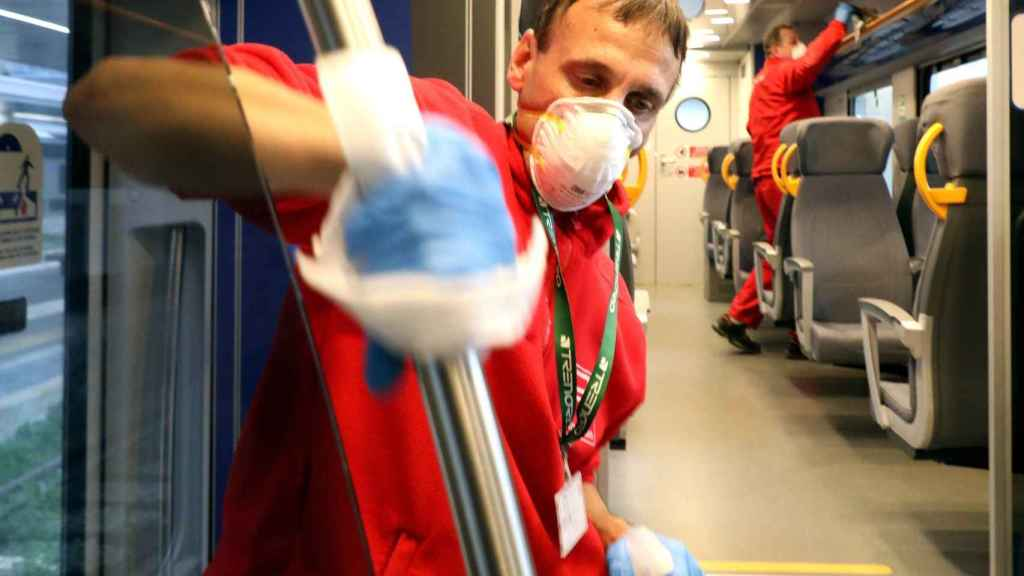 Unos operarios desinfectan un tren.