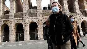 Una joven con mascarilla delante del coliseo romano.