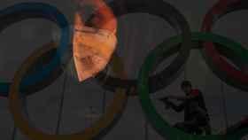 Los aros olímpicos junto a una mujer que porta una máscara por el temor al contagio del coronavirus