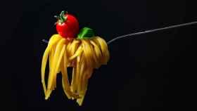 Un tenedor con unos espaguetis y un tomate.