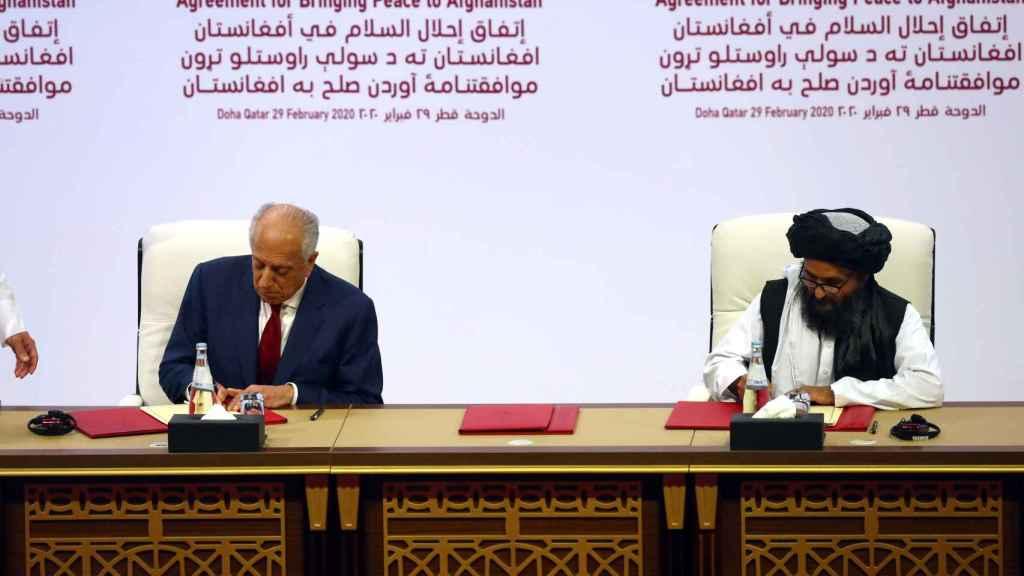 El líder talibán, Mullah Abdul Ghani Baradar, y el representante especial para la paz de EEUU, Zalmay Khalilzad, firmando el acuerdo.