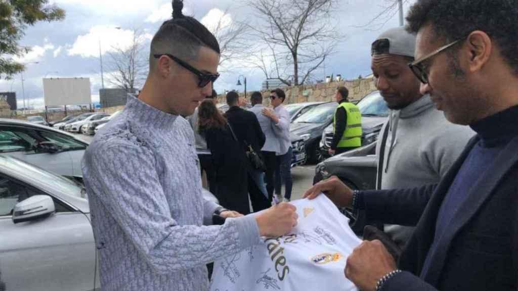 Cristiano Ronaldo firmando una camiseta del Real Madrid