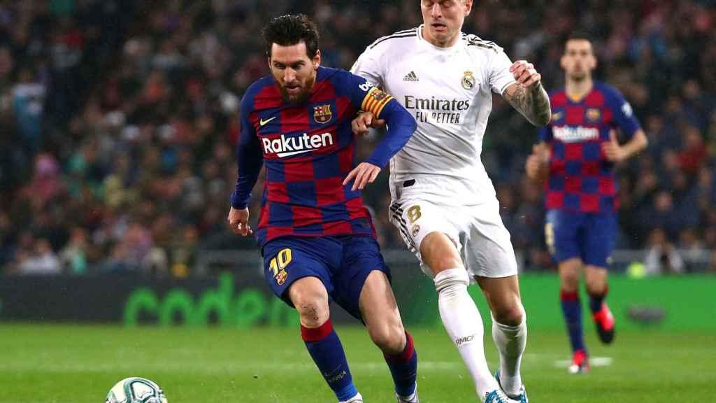 Toni Kroos intenta robar el balón a Leo Messi