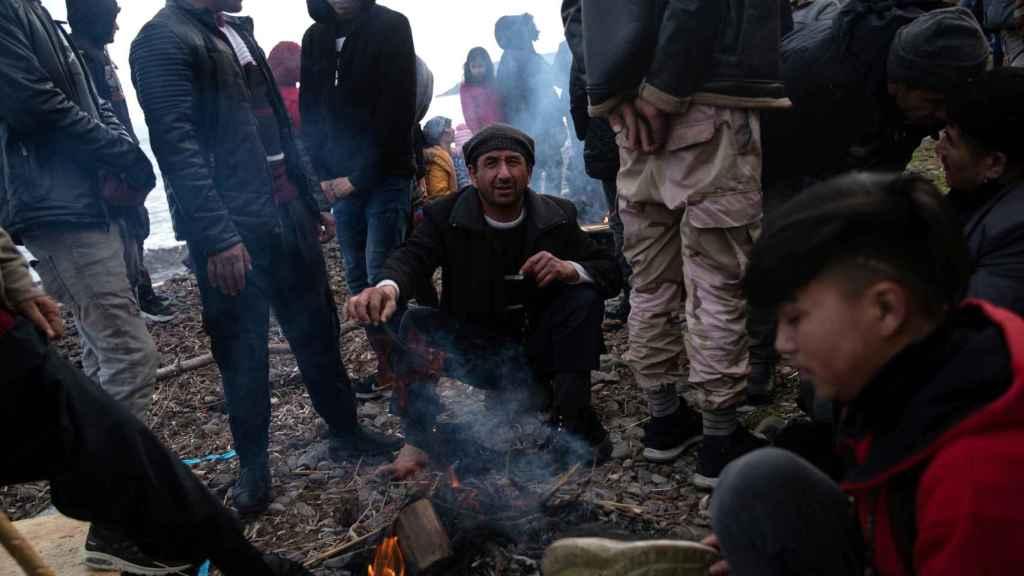 Migrantes se calientan junto a las hogueras después de cruzar parte del Mar Egeo desde Turquía.