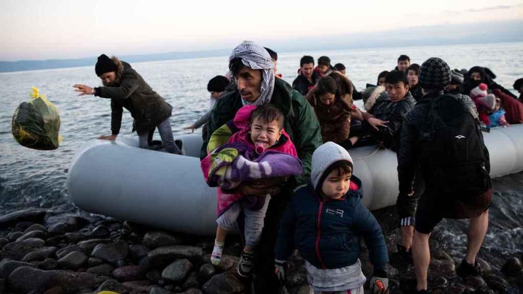 Migrantes de Afganistán llegan a un bote en una playa cerca del pueblo de Skala Sikamias.