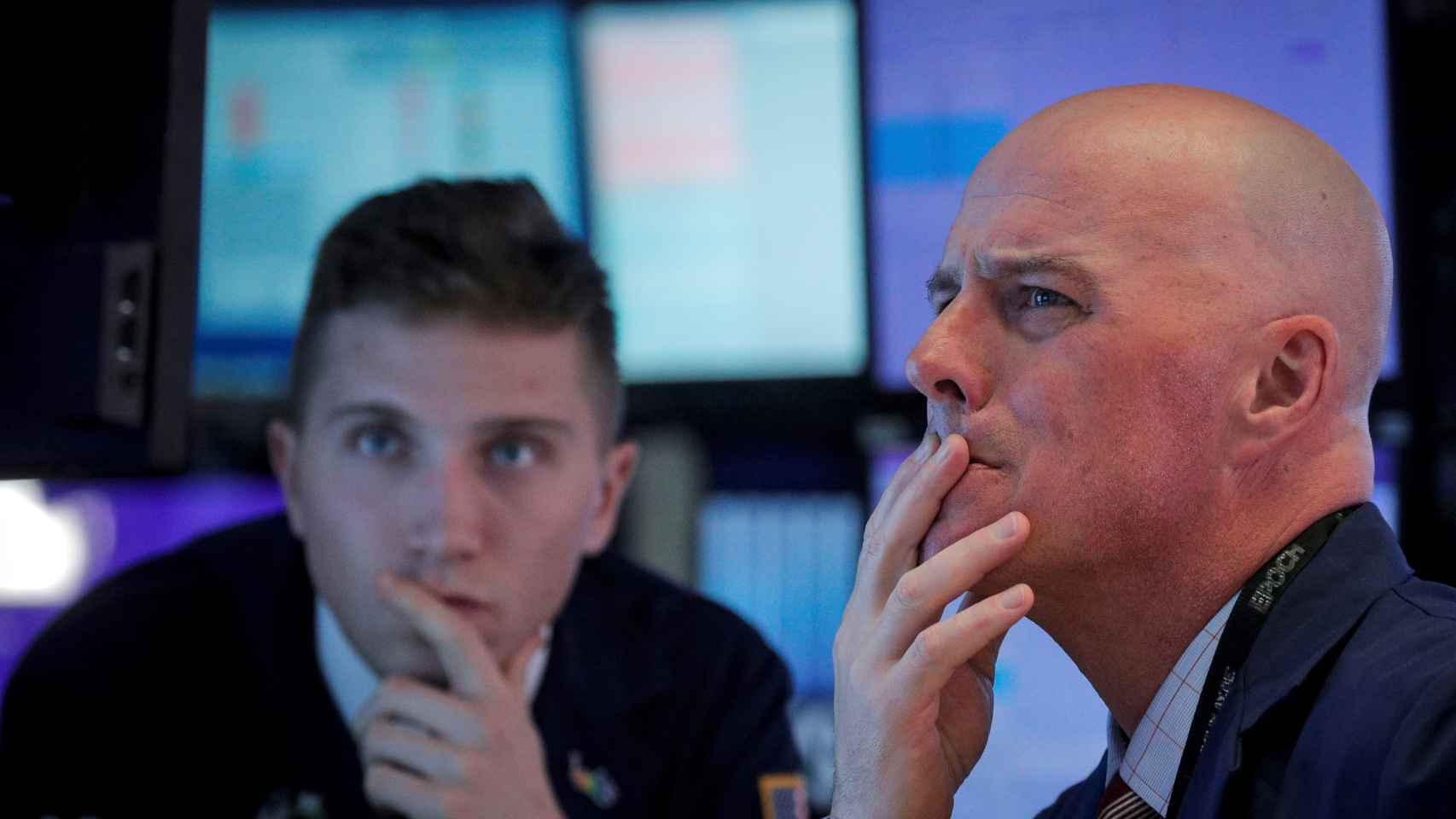 Dos brókeres observan pantallas de negociación de valores.