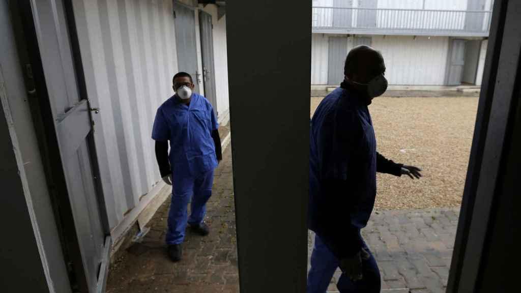 Trabajadores de salud palestinos usan mascarillas en una zona de cuarentena instalada por el Ministerio de Salud para evaluar a los pasajeros que regresan de China por coronavirus, en el sur de la Franja de Gaza.