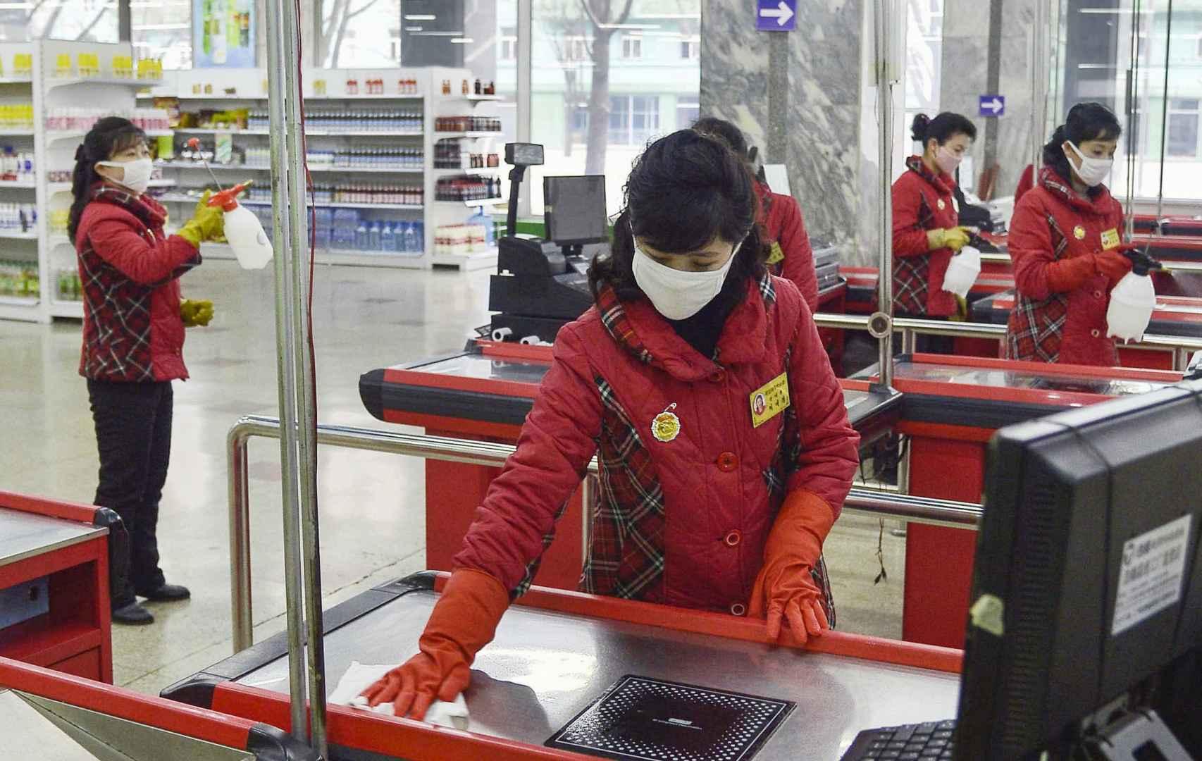 Trabajadoras de una tienda desinfectan el espacio en Pyongyang.