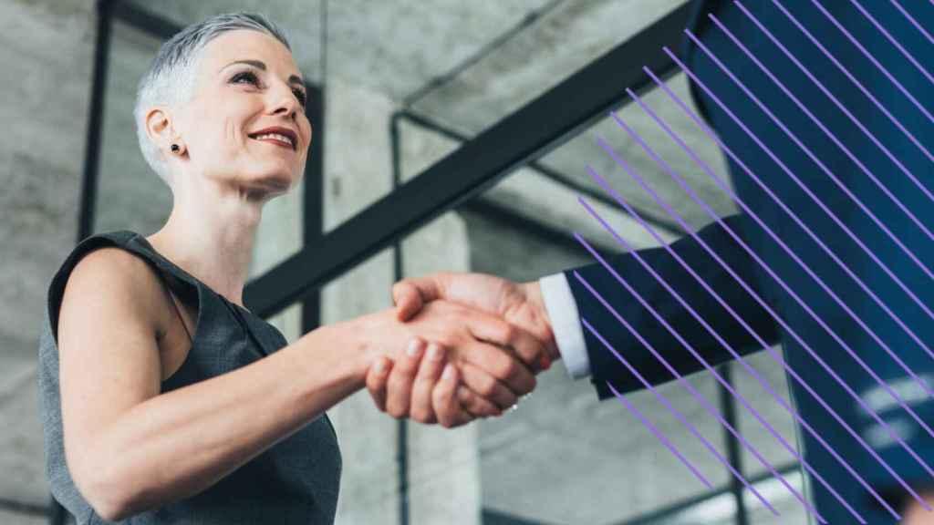 Una mujer directiva saluda a un trabajador.