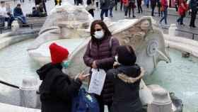 Un grupo de personas con mascarilla en una ciudad de Italia.
