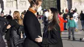 Una pareja con mascarillas se mira en Pisa