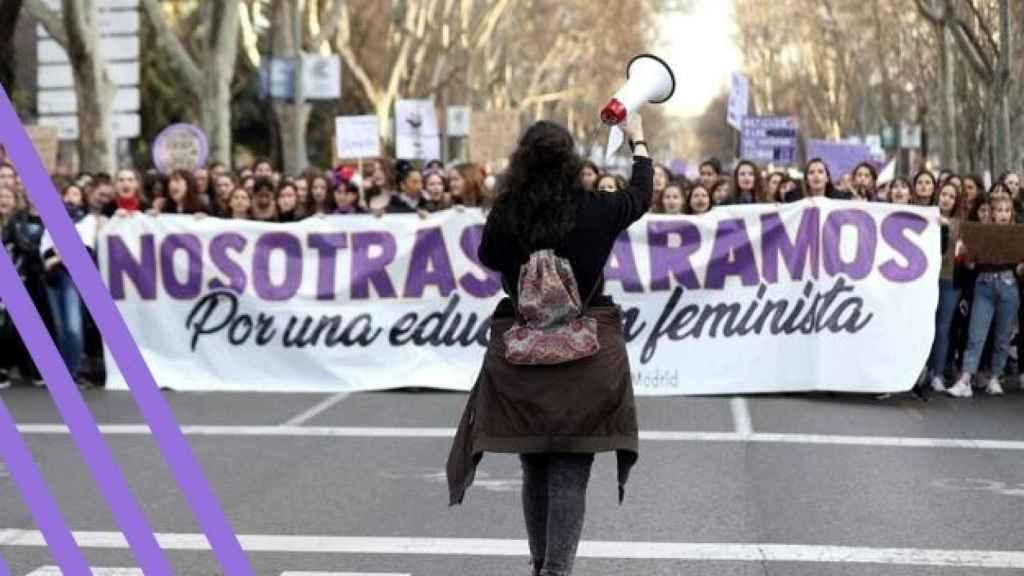 Una manifestante frente a una pancarta con el lema de 2018.