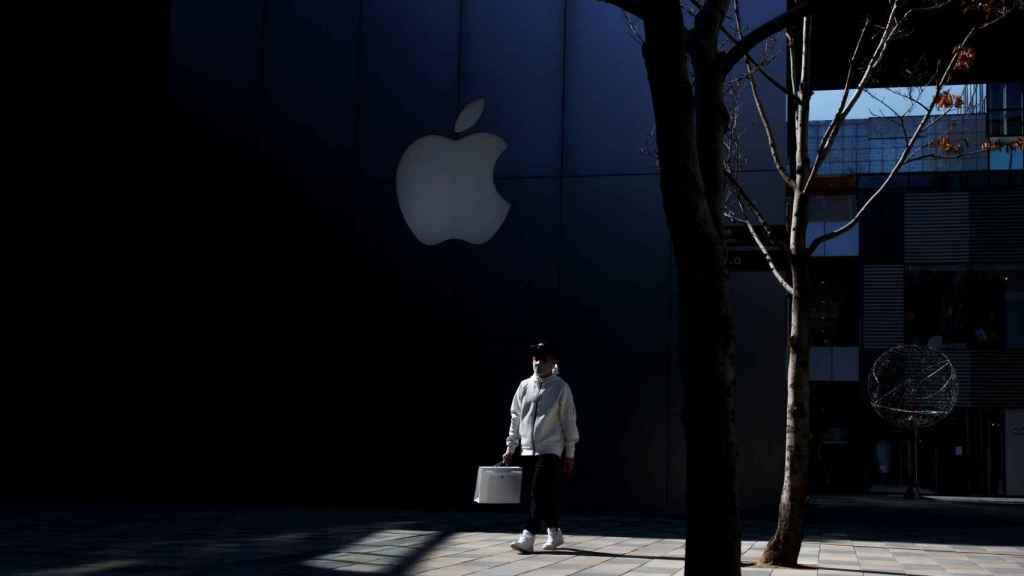 Una persona con mascarilla pasa al lado de una Apple Store en Beijing