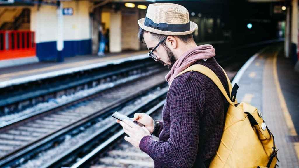 Hombre utilizando su smartphone ante las vías del tren.