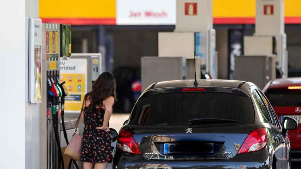 Una mujer repostando en una gasolinera.