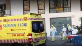 La menor, con un traje de aislamiento, sale con el personal sanitario de los Servicios del 112.