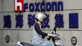 Un motorista pasa por delante de la sede de Foxconn de Taipei.