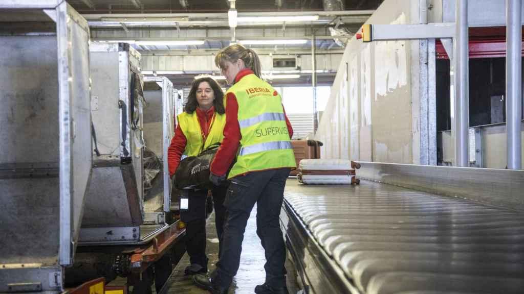 Las auxiliares de servicio de carga colocan las maletas en los contenedores.