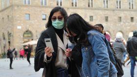 Ciudadana con mascarilla utilizando un móvil.