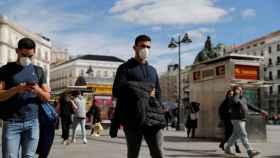 Dos jóvenes caminan con mascarilla por la Puerta del Sol de Madrid.
