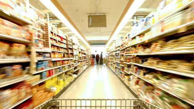Un pasillo de un supermercado visto desde un carrito de compra vacío.
