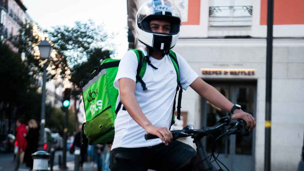 Alfredo, el único repartidor con bici que lleva casco de moto, según sus compañeros.