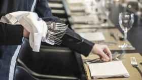 Un camarero pone la mesa en un restaurante.