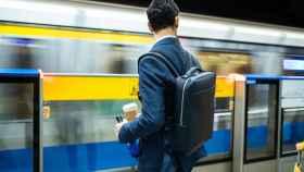 Un trabajador de un distrito financiero espera el tren con mochila.