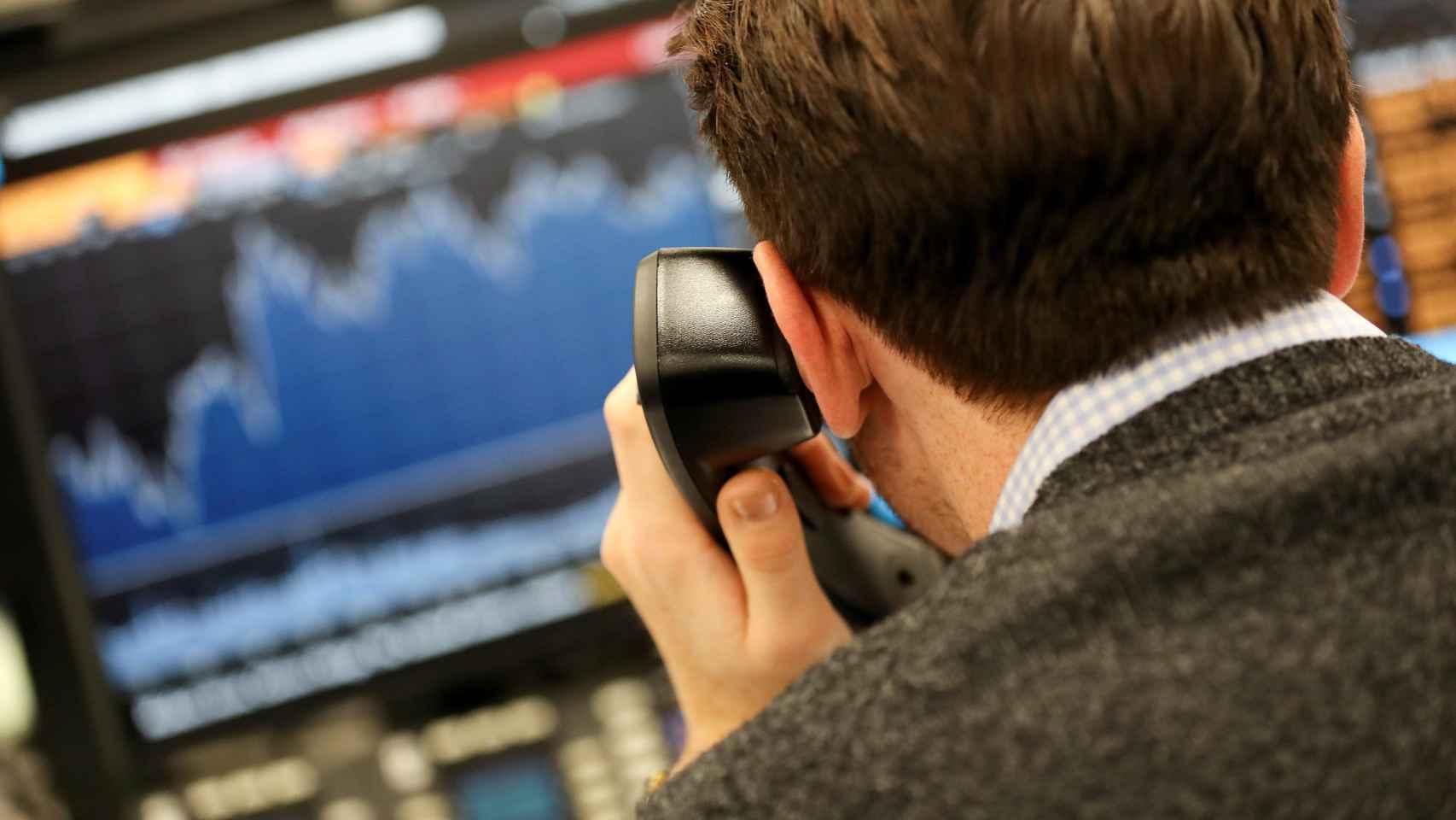 Un bróker consulta pantallas de cotización mientras lanza órdenes telefónicas.