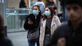 Dos jóvenes con mascarilla por las calles de Barcelona.