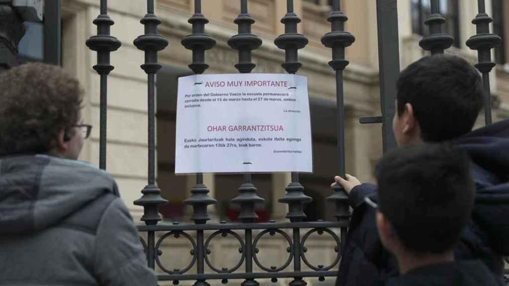 Dos escolares leen el cartel informativo sobre el cierre del colegio en Bilbao.