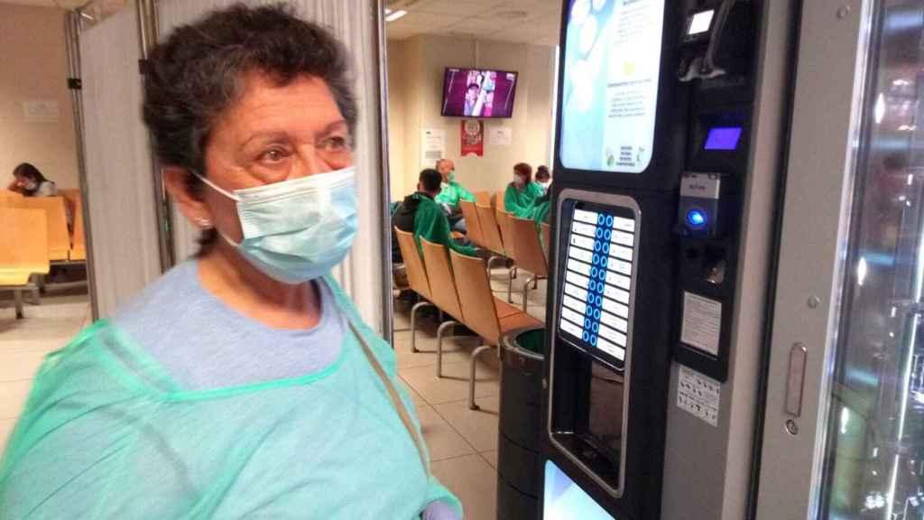 Una señora que espera que le hagan las pruebas del coronavirus tras un biombo.