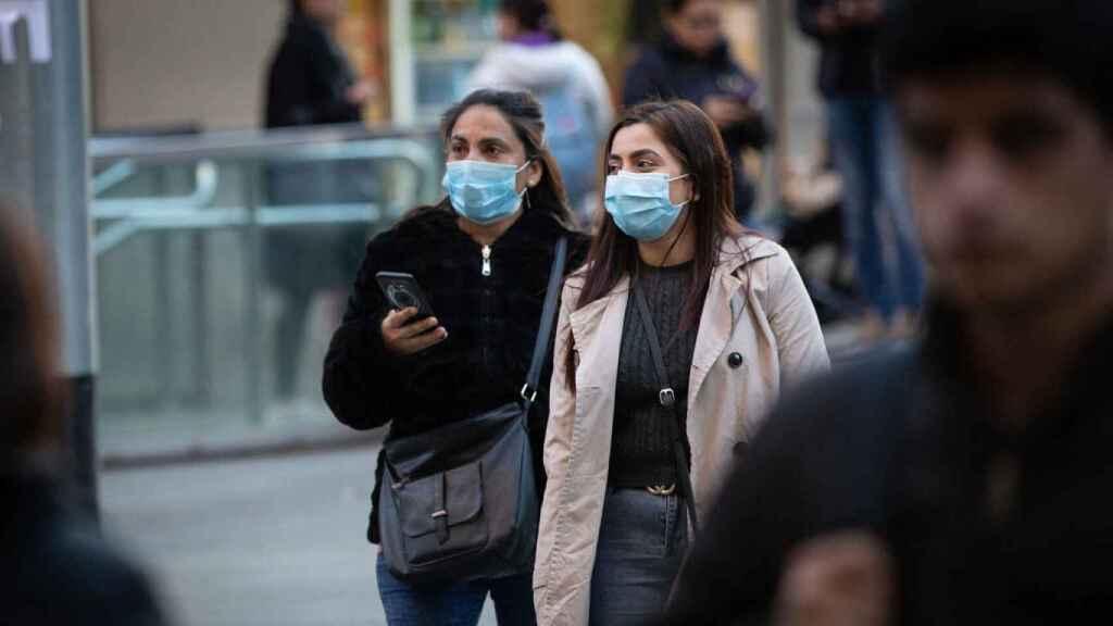 Dos mujeres pasean por la calle con mascarillas.