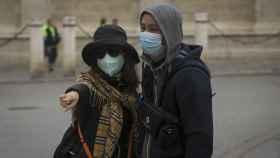 Dos turistas con mascarillas.