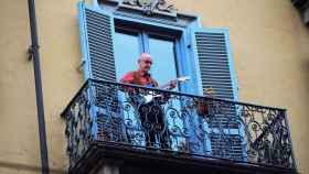 Un hombre toca la guitarra desde el balcón de su casa, en Turín.