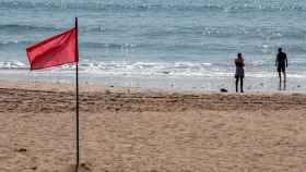 Una pareja disfruta del buen tiempo en una playa de Chiclana de la Frontera.