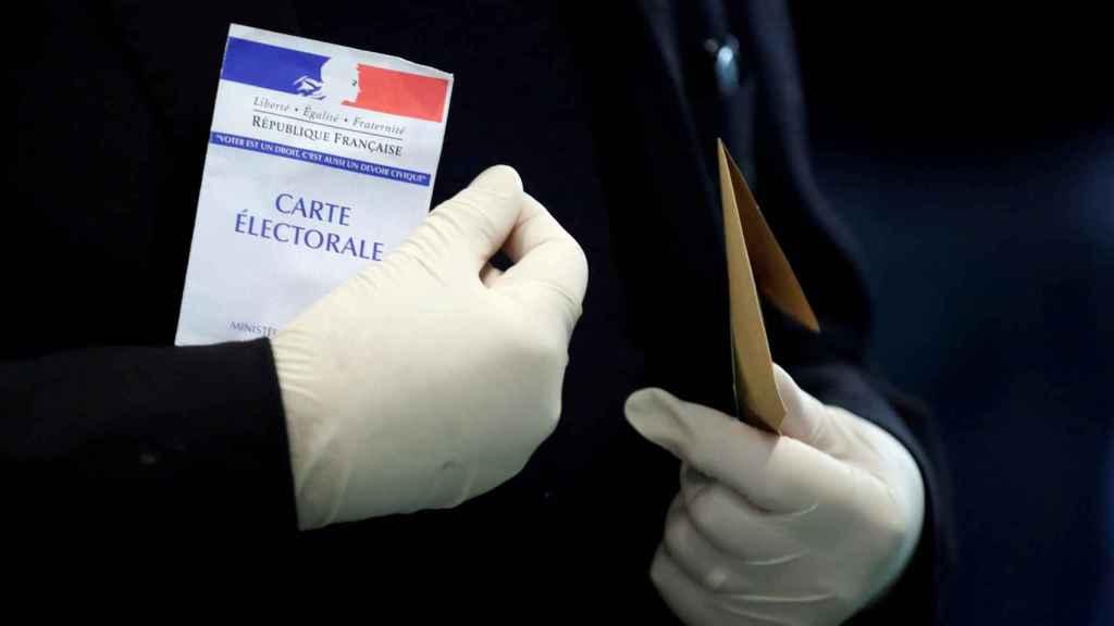 Un hombre con guantes de látex porta su tarjeta electoral antes de votar, en París.