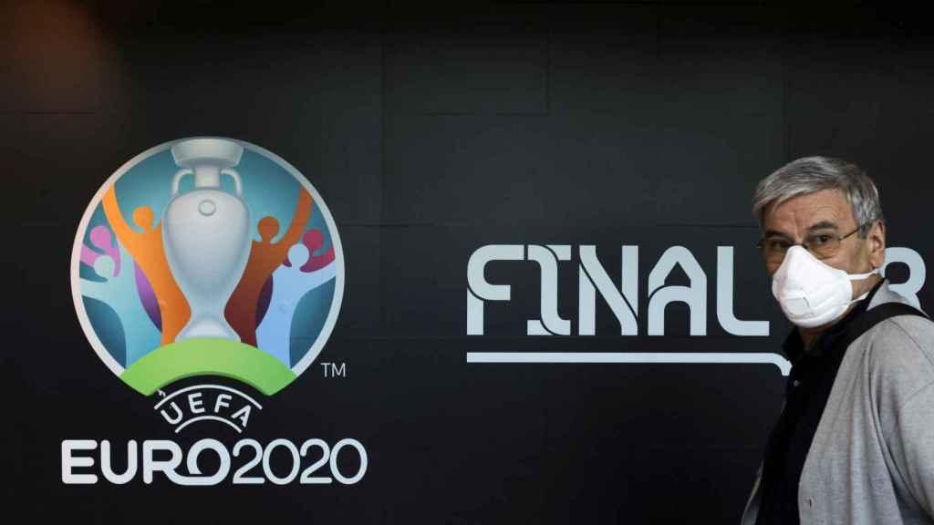 El logo de la Eurocopa 2020 y un empleado de UEFA con mascarilla