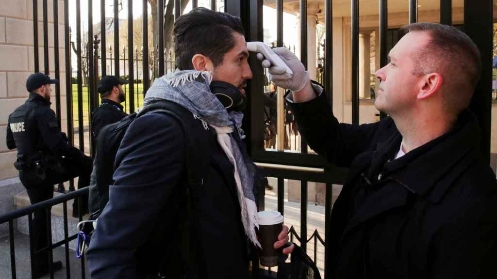Personal de la Casa Blanca toma la temperatura a los funcionarios de la entidad.