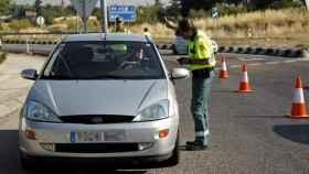 Un agente de la Guardia Civil para a un vehículo en un control.